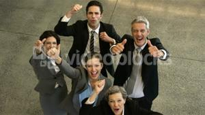 Business people cheering with thumbs up