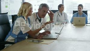 Concentrated doctors looking at laptop