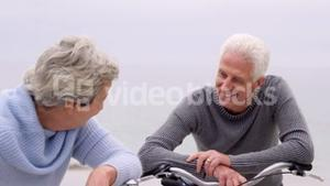 Retired couple laughing with bikes