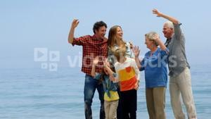 Multi generation family jumping on the beach
