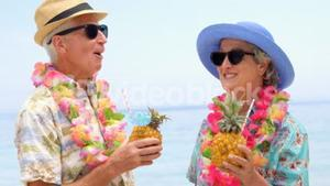 Retired couple drinking cocktails on the beach