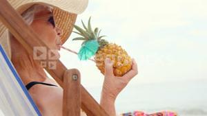 Retired woman drinking cocktail and lying on deckchair
