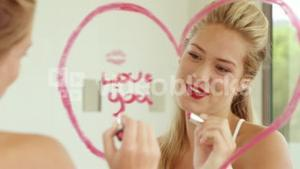 Smiling woman writing love words on the mirror