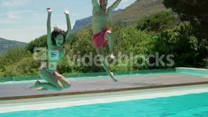 Couple jumping in the swimming pool