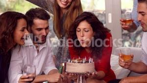 Woman blowing out candle on her birthday cake