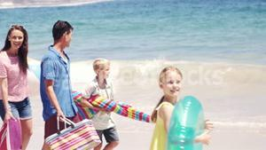 Young family walking together with picnic stuff