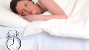 Alarm clock ringing while a cute woman is sleeping
