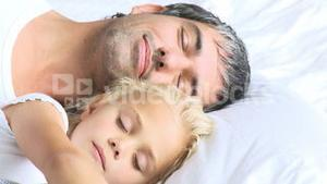 Father and daughter sleeping in a bed