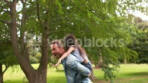 Handsome father giving piggy back to his daughter