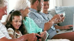 Cute family using electronic devices on the couch
