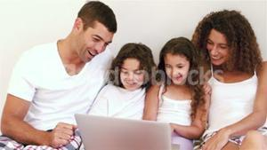 Cute family using laptop computer on their bed