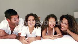Cute family laughing on their bed
