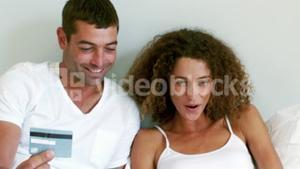 Cute couple doing online shopping in their bed