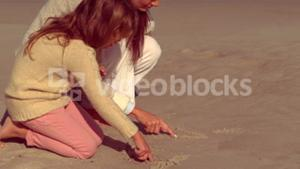 Mother and daughter writing on sand