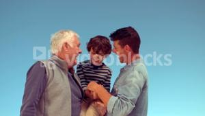 Father and grandfather tickling boy
