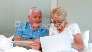 Senior couple using tablet and laptop