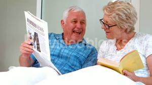 Smiling senior couple reading newspaper