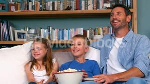 Family eating popcorn while watching tv