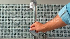 Hand opening a water tap