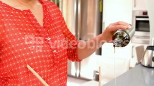 Woman pouring olive oil over salad