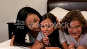 Family resting in bed together