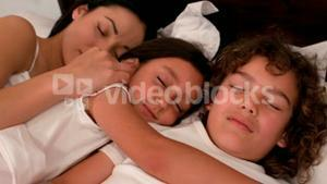 Happy family sleeping in bed