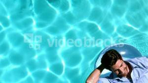 Businessman lying on buoy in swimming pool