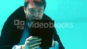 Businessman using his tablet underwater