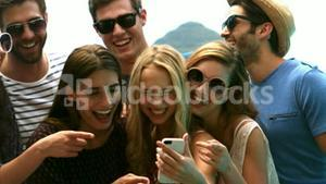 Happy friends watching a smartphone