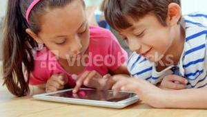 Smiling children playing with tablet