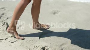 Woman walking on the beach bare footed