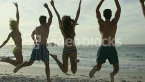 Friends jumping on the beach