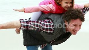 Father giving piggy back to daughter