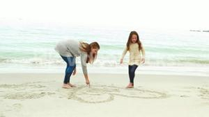 Mother and daughter drawing on the sand