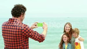 Father taking a picture of her family