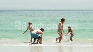 Happy family playing in water