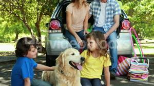 Family with dog next to car