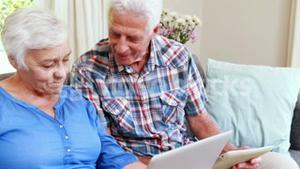 Senior couple on laptop and tablet