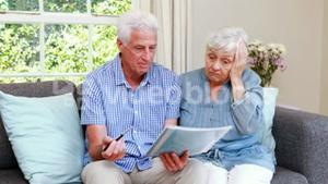 Worried senior couple looking at document