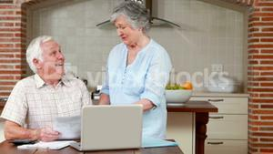 Senior couple paying their bills with computer