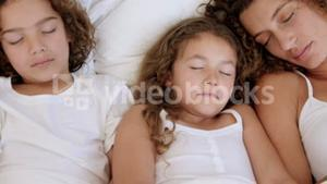 Family sleeping on bed together