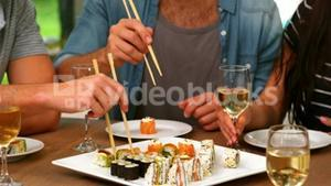 Happy friends eating sushi