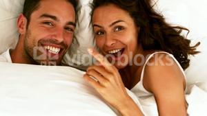 Happy couple having fun in the bed at home