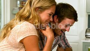 Happy couple using laptop in kitchen in slow motion