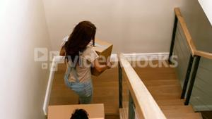 Happy couple entering in their new home with moving box