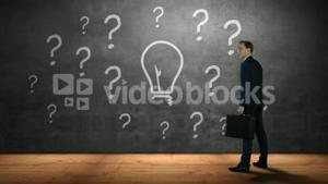 Businessman looking at question marks and bulb