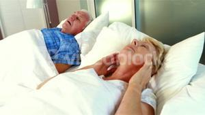 Senior woman blocking out his husband snoring