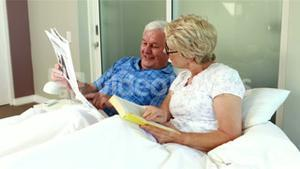 Senior couple reading book and newspaper