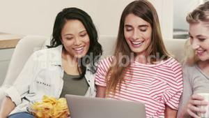 Female friends watching a movie on laptop