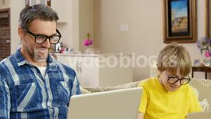 Smiling father and son using laptops
